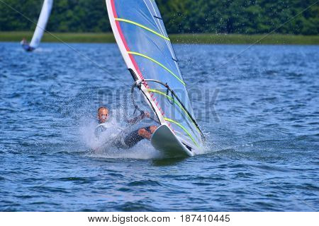 Man on a windsurfing board on the lake