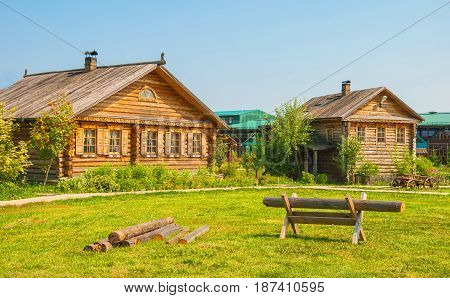 Lawn in a village street with log houses