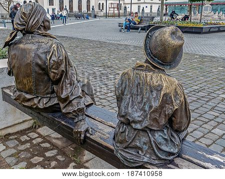 ALBA IULIA ROMANIA - APRIL 30 2017: Group of bronze statues in Alba Carolina Citadel Fortress square depicting one old woman and child on bench symbolizing medieval time.