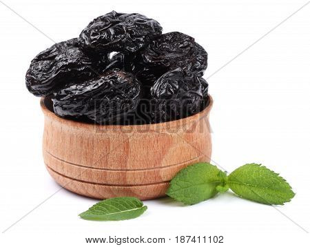 Dried plums - prunes in wooden bowl isolated on white background