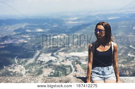 Hipster young girl with backpack looking on observation deck and planning travel plan. View tourist traveler on background panoramic view of the city mockup summer in Barcelona