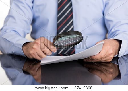 Businessman examines the contract with a magnifying glass