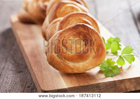 Phyllo pastry cheese pies served on wooden board