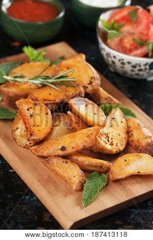 Spicy roasted potato wedges with herbs and salad