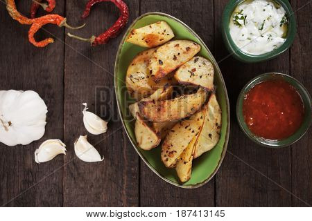 Spicy roasted potato wedges with tomato sauce and sour cream