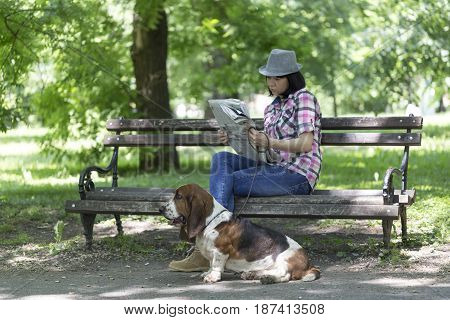 She Loves Her Dog. A Woman Sits On A Bench In The Park With His Beautiful Dog And Reading The Newspa