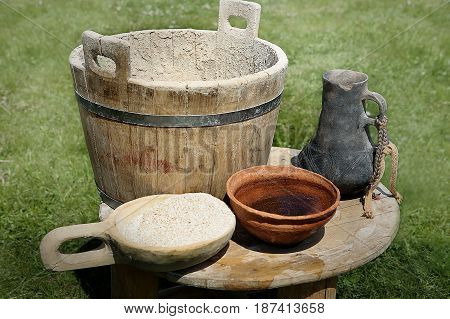 Medieval ware: wooden tub and ladle with flour, ceramic pitcher and bowl. Medieval ware for preparing dough and baking bread.