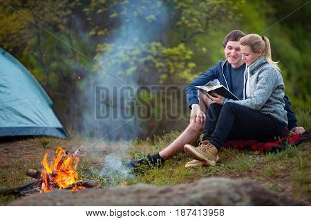 Happy young couple sitting near campfire and reading book