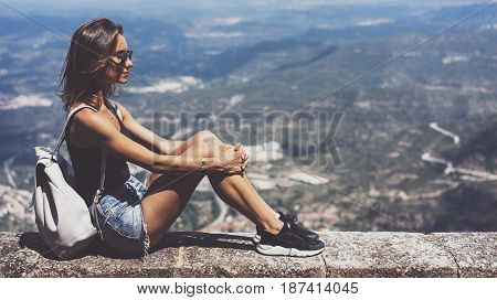 Hipster young girl with backpack and sun glasses looking on observation deck and planning travel plan. View tourist traveler on background panoramic view of the city mockup summer in Barcelona