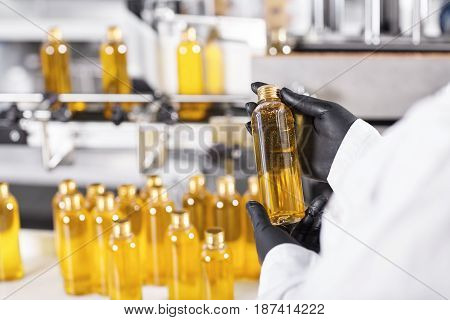 Horizontal Portrait Of Mass Process At Factory. Researcher Standing Near Many Bottles With Yellow Li