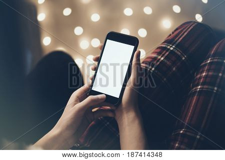 Hipster girl using mobile phone in a home atmosphere person holding smartphone on background glow bokeh Christmas illimination female hands texting on relax glitter xmas decoration mockup templates blur