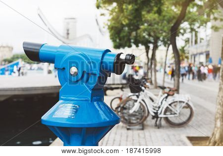 Touristic telescope look at the city with view of Barcelona Spain close up old blue binoculars on background viewpoint the port yacht and cycle bike coin operated in panorama observation nature mockup