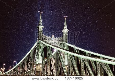 Liberty green Bridge at night in Budapest with illumination and starry sky, outdoor travel city background