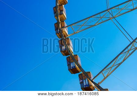 Fragment of Ferris wheel against blue sky, outdoor entertainment fun leisure concept