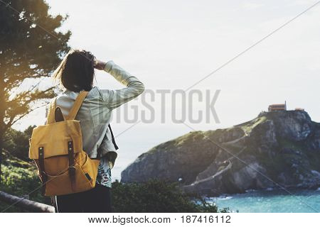 Hipster young girl with backpack enjoying sunset on seascape on peak mountain. Tourist traveler on background valley landscape view mockup. Hiker looking sunlight ocean in trip holiday in basque island Gaztelugatxe