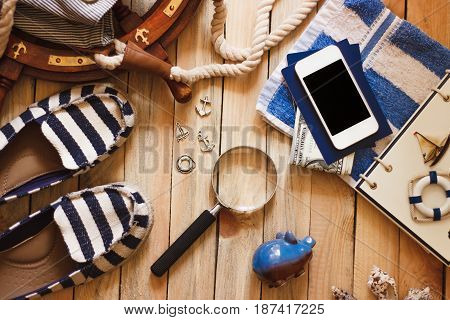 Striped Slippers, Towel, Piggy Bank, Phone And Maritime Decorations, Wooden Background