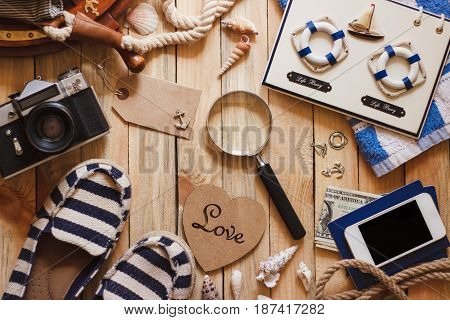 Striped Slippers, Camera, Phone And Maritime Decorations On The Wooden Background