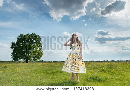 A Beautiful Young Free Girl In A Light Dress With Lemons In The Middle Of A Spacious Field With A Bi