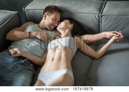 Tender couple with closed eyes lies on the sofa and holds their left hands together. Guy in blue jeans and light sleeveless holds a rose in right hand. Girl wears a gray underwear. Indoors. Closeup.