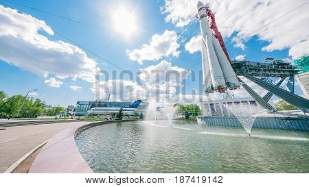 Moscow, Russia - May 18, 2017:  fountain under soviet spaceship Vostok in the park of VDNKh - Exhibition of Achievements of National Economy. Wide view to plane exposition and Ostankino TV tower