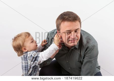 Hearing aids in the Family - Toddler boy examining his father's hearing aid in his ear