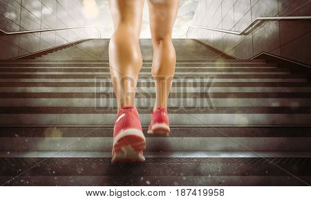 Legs of sports woman climbs stairs running