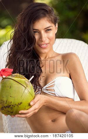 Beautiful girl refreshing with coconut water