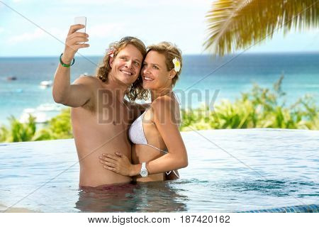 Happy couple taking selfie in tropical resort