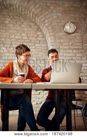 Deadline on design working- designer couple working late at computer in office