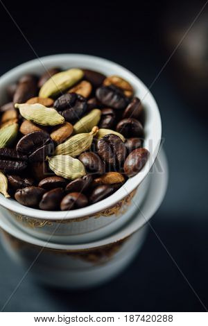 Roasted coffee beans with aromatic green cardamom pods in traditional qahva cups. A popular arabic cardamom flavoured coffee ingredients.