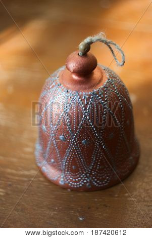 closeup photo of a bell on a rope made of clay, painted clay, old wooden table