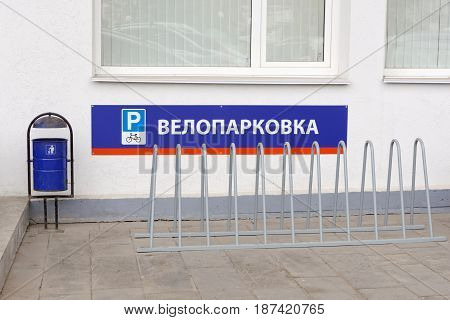 Metal Bicycle parking. On the plate there is a parking sign a painted bicycle and a bicycle parking is written.