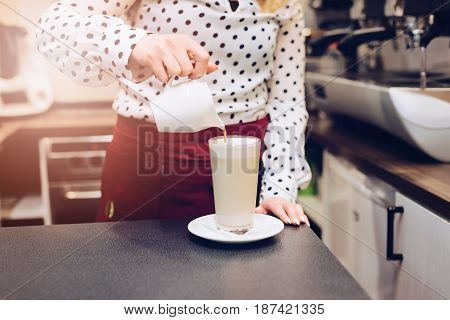 Woman Barista Pouring Coffee To Foamed Milk.
