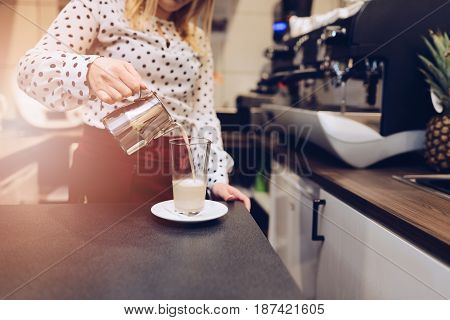 Cafe Employee Barista Pouring Hot Foamed Milk To Glass