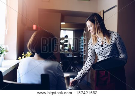 Young Waitress In Apron Serving Coffee Latte