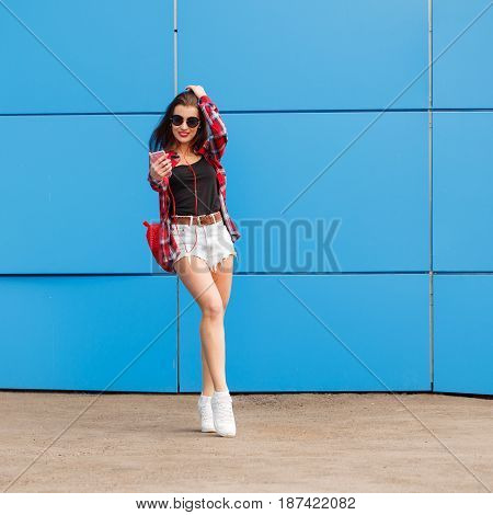Fashion portrait of pretty smiling and woman in sunglasses with smartphone and headphones against the colorful blue wall. Make selfie. Outdoor