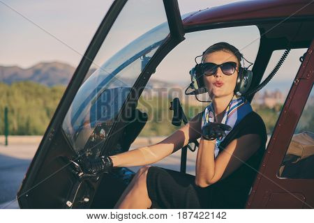 Attractive woman pilot sitting in the helicopter and blowing a kiss