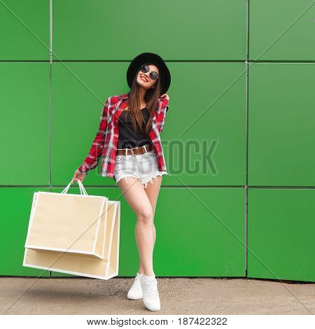 Portrait of beauty fashion smiling woman with shopping bags in sunglasses on green background. Outdoor