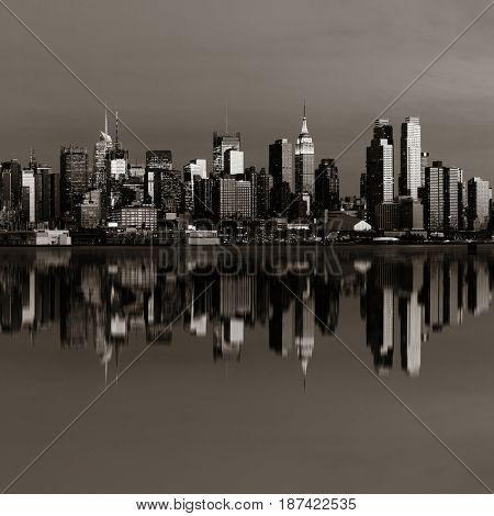 Midtown Manhattan skyline with reflections at dusk panorama over Hudson River in black and white