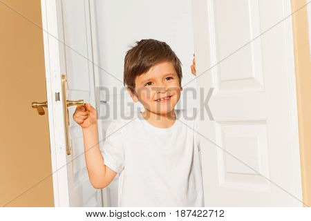 Portrait of smiling six years old boy holding door-handle while opening the white door at home