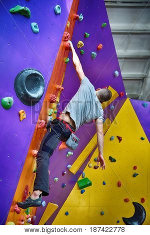 Climber On Artificial Climbing Wall In Bouldering Gym Without Insurance.
