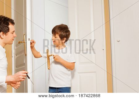 Portrait of happy young father and kid son installing door handle together