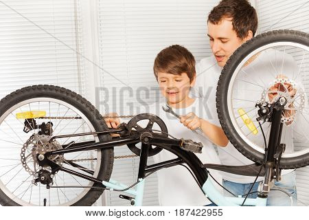 Young father teaching his six years old son repairing bicycle using spanner