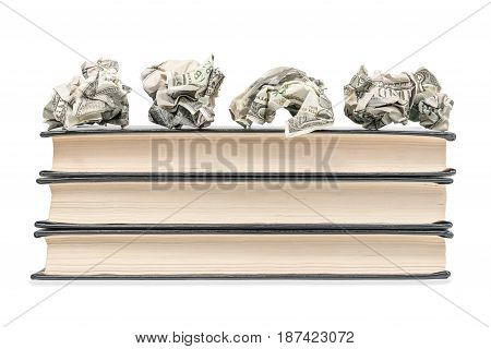 Crumpled money lying on top of a pile of closed books isolated on a white background