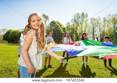 Portrait of lovely blonde girl waving rainbow parachute standing outdoors in a circle with her friends