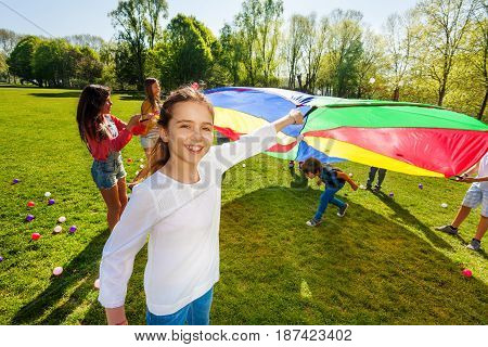 Portrait of smiling girl playing rainbow parachute together with her friends in the park