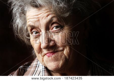 Thoughtful and sad elderly woman on a black