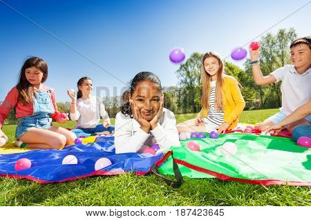 Portrait of cute African boy laying on the colorful mat on the lawn, while her friends throwing balls in the air