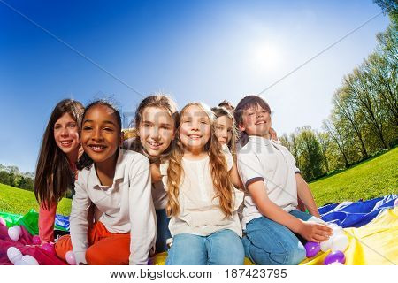 Group of six happy kids sitting in line on colorful mat in the park at sunny day