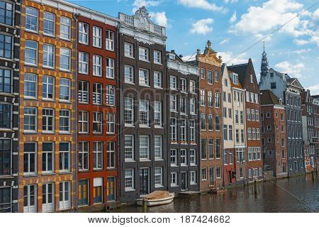Traditional dutch old houses in center of Amsterdam Netherlands Europe. Typical historic buildings on canal in Amsterdam. Colorful facades of dutch dancing houses. Beautiful summer cityscape